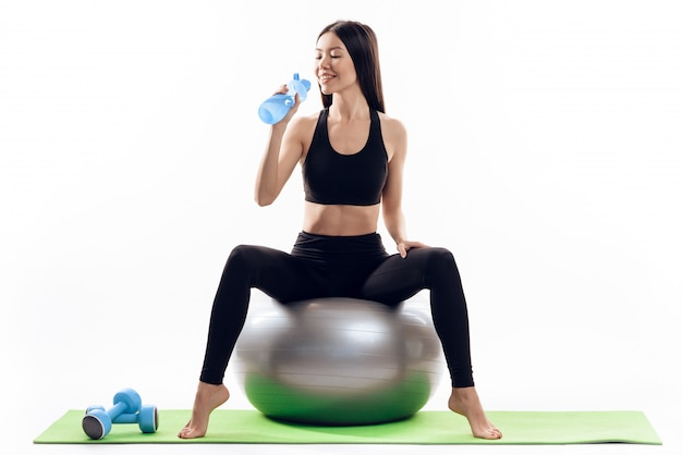 Asian girl sits on gym ball and drinks water.