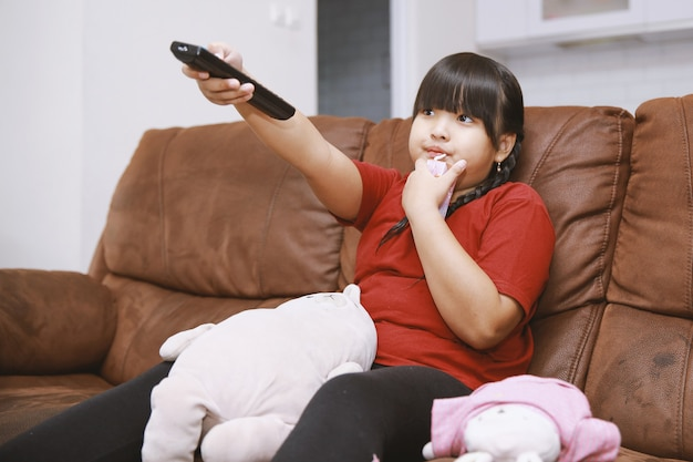 Asian girl sitting on couch with remote control watching movie on television in living room