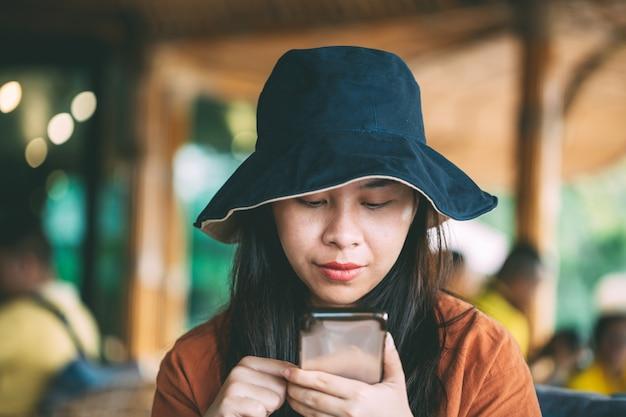 休暇中にソーシャルメディアの携帯電話を再生しているコーヒーショップに座っているアジアの女の子、休日のカフェでリラックスしている女の子、かわいい女の子の肖像画。