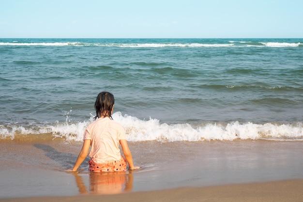 ビーチに座っているアジアの女の子