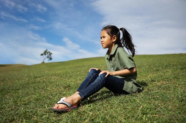 Азиатская девушка сидит на холме с зеленой травой, чтобы наслаждаться красивой природой в летнее время