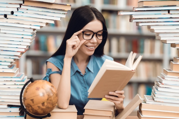 Asian girl sitting at table surrounded by books in library.