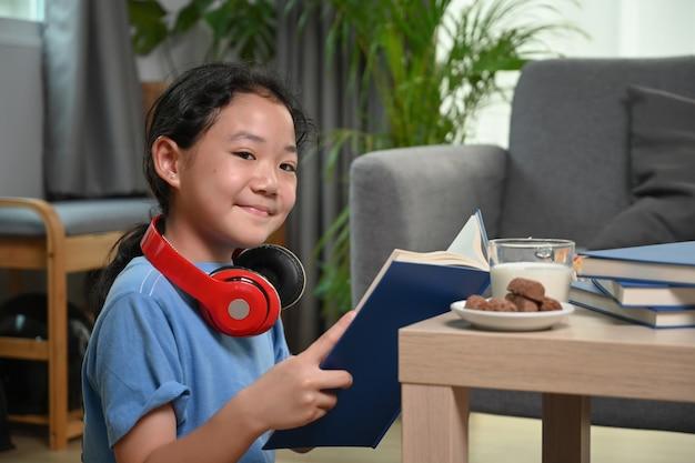 Азиатская девушка улыбается и держит книгу, сидя на полу в гостиной.