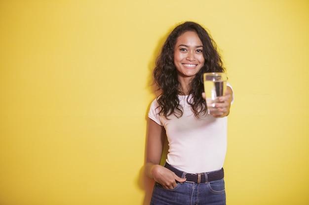 Азиатская девушка улыбается, предлагая стакан минеральной воды