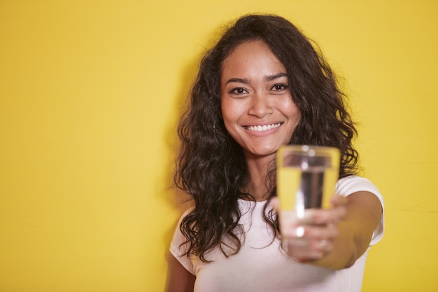 Asian girl smiling while offering a glass of mineral water