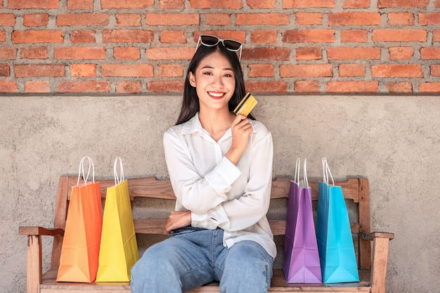 クレジットカードと買い物袋を持って笑っているアジアの女の子は、表情をリラックスして買い物を楽しんでいます