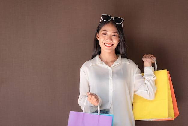 リラックスした表情で買い物を楽しんで買い物袋を持って笑顔アジアの女の子