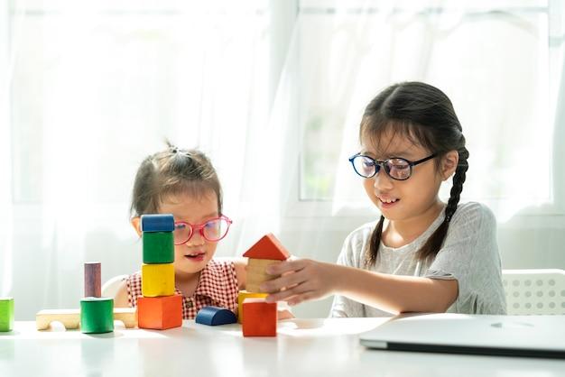 아시아 소녀는 거실에서 여동생과 함께 나무 블록 장난감을 연주하기 위해 좋은 시간을 보냅니다.