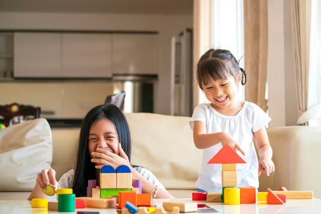 Asian girl spend quality time together for playing wooden block toy with her sister in living room at home. asian family and kids concepts