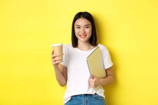 Studentessa asiatica che beve caffè e tiene in mano un laptop, sorride alla telecamera, in piedi su sfondo giallo