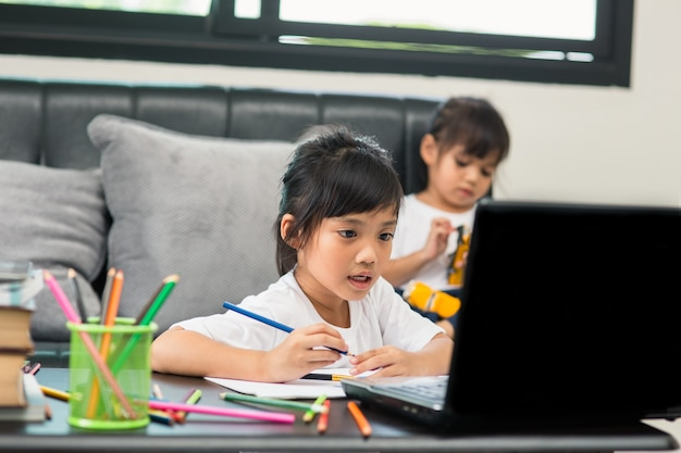 Asian girl student online learning class study online video call zoom teacher, happy girl learn english language online with laptop at home.new normal.covid-19 coronavirus.social distancing.stay home