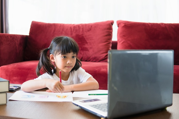 アジアの女子学生のオンライン学習クラスは、自宅のラップトップでオンラインで勉強します。