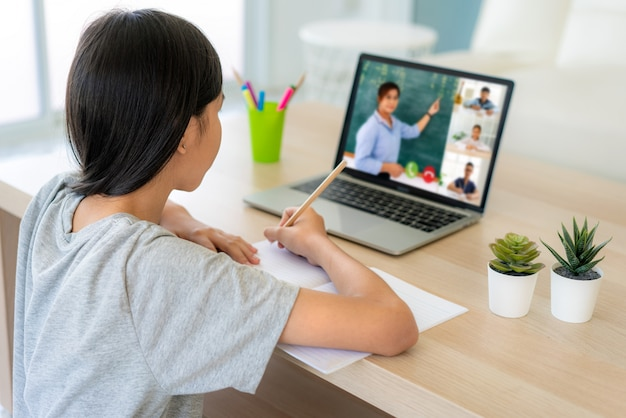 집에서 거실에서 컴퓨터에 교사와 급우들과 함께 아시아 소녀 학생 화상 회의 전자 학습