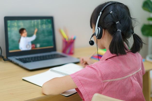 아시아 여자 학생 화상 회의 e- 학습 교사와 집에서 거실에있는 컴퓨터에 급우.