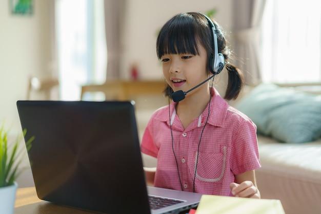 自宅の居間でコンピューター上で教師やクラスメートとeラーニングを行うアジアの女子学生のビデオ会議。