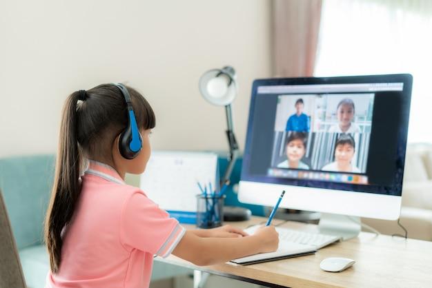 リビングルームのコンピューターで教師とクラスメートとアジアの女子学生のビデオ会議eラーニング