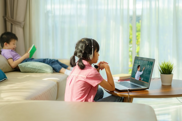 Asian girl student video conference e-learning with teacher and classmates on computer and her sibling reading book in sofa in living room at home