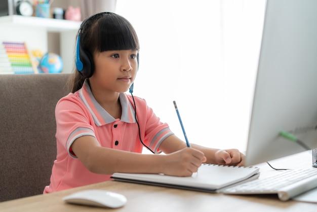 Азиатская девушка студент видеоконференции электронного обучения с учителем на компьютере в гостиной дома.