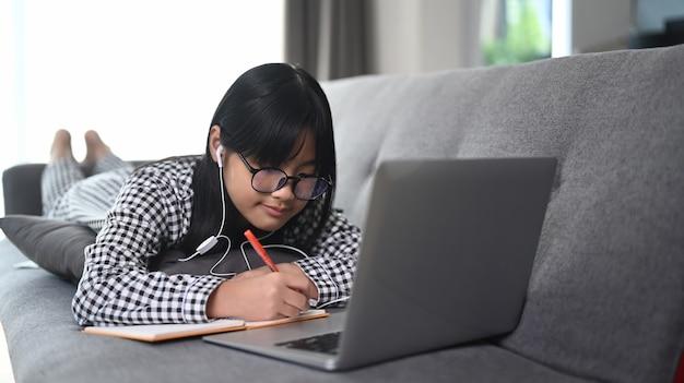 自宅の居間でラップトップコンピューターで教師と学ぶアジアの女子学生のビデオ会議e。遠隔教育の概念。