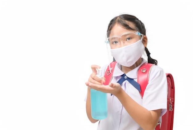 아시아 여자 학생 착용 얼굴 방패와 알코올 젤을 들고 마스크.