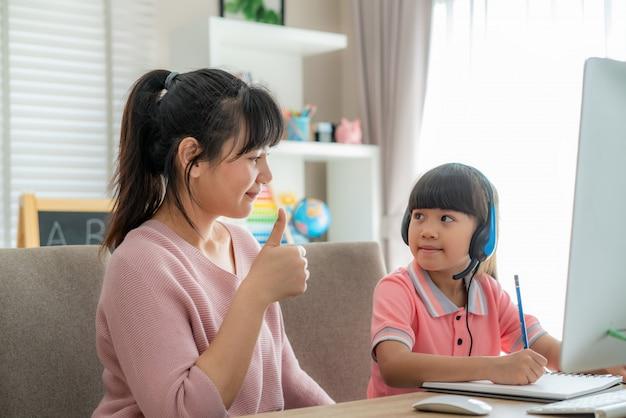 화상 회의 동안 그녀의 딸까지 어머니 엄지 손가락으로 아시아 여자 학생