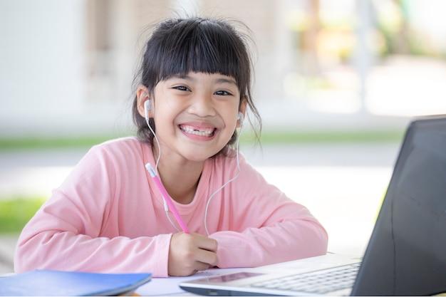 アジアの女子学生のオンライン学習クラスは、自宅でノートパソコンを使って勉強します。