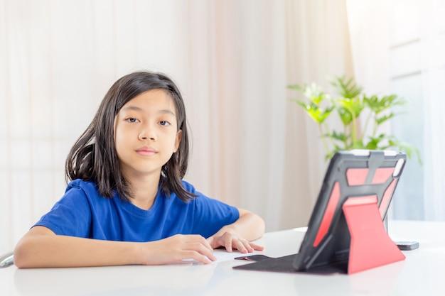 Азиатская девушка учится онлайн в гостиной дома с планшетом
