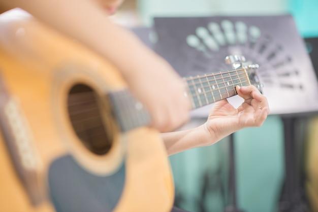 Asian girl studyguitar in the music classroom