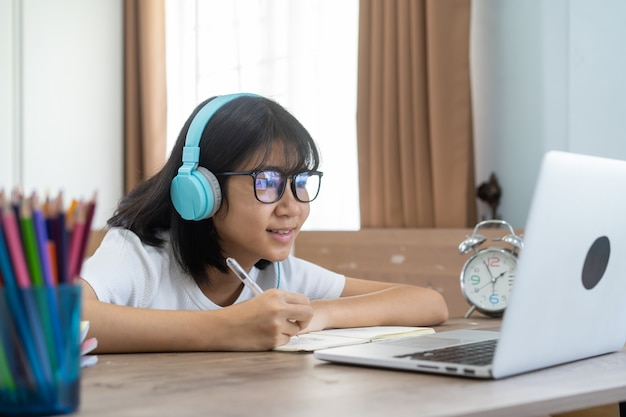 Asian girl studying homework online lesson at home, social distance online education idea concept