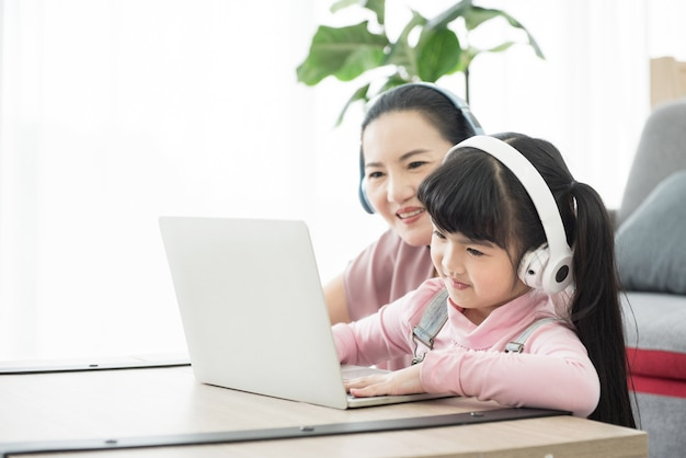노트북과 헤드셋으로 공부하는 아시아 소녀, 사회적 거리를 두는 통신 과정