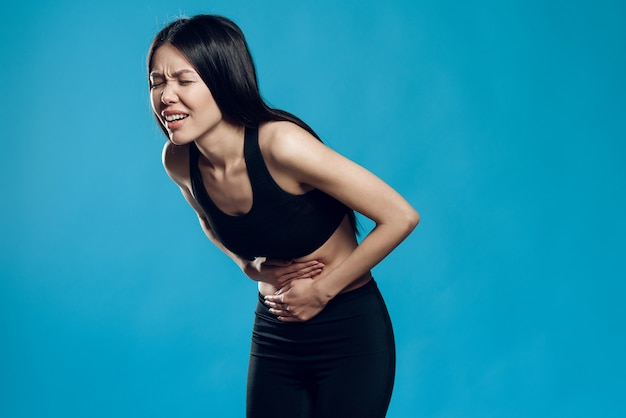 Asian girl suffers from a pain in the stomach.