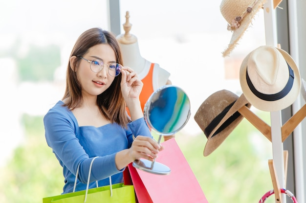 アジアの女の子のティーンは、ファッションアクセサリーショップでメガネを試着し、眼鏡をテストしています。