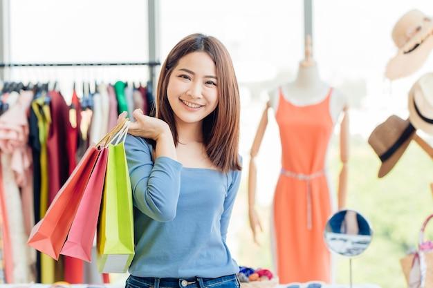 Азиатская девушка подросток с много хозяйственной сумкой. счастливого дня распродажи в магазине