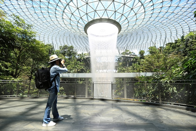 Asian girl traveler with backpack enjoying with holding dslr camera in his hands with talking pictures to beautiful rain vortex at jewel changi airport in singapore
