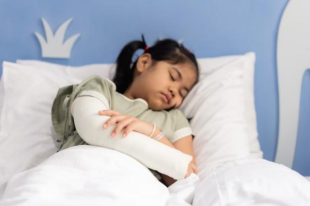 手術から戻って腕を骨折して痛いベッドに横たわっている病院でのアジアの女の子の治療。