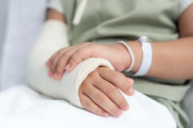 Лечение азиатской девушки в больнице, лежащей на кровати, больно сломанной рукой после операции.