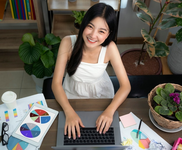 Asian girl typing data to her computer notebook for prepare her report
