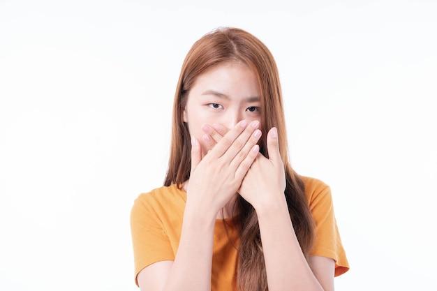 アジアの女の子は、白い背景での検疫コロナウイルスcovid19の発生時に保護のために彼の口を覆って閉じた両手を使用し、スプレッドcovid-19を保護します