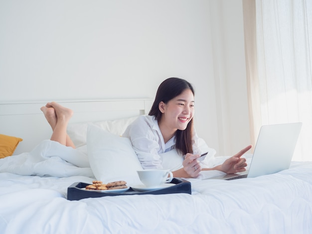 Asian girl using computer with credit card on bed