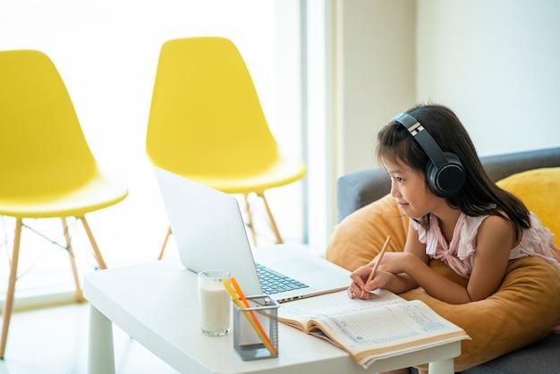 自宅検疫中にオンライン学習ホームスクーリングのためにデスクトップコンピュータを使用しているアジアの女の子。