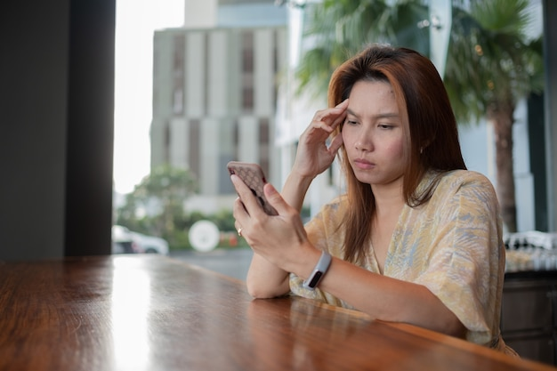 スマートフォン、モバイルを見ている女性を使用してアジアの女の子