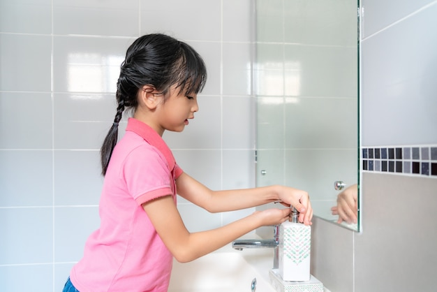 Asian girl washing hands with soap under the faucet with water in bathroom at home.