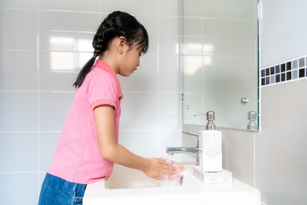 Asian girl washing hands with soap under the faucet with water in bathroom at home