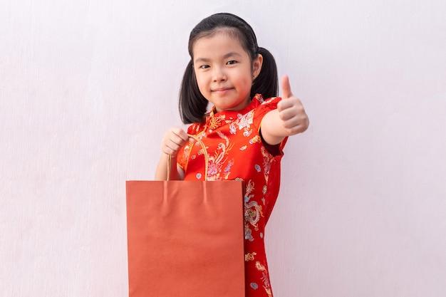 아시아 여자 착용 치파오 잡고 쇼핑 종이 봉지. 중국의 설날.