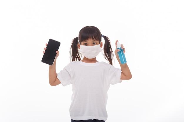 アジアの女の子がアルコールでスマートフォンの画面をクリーニングするマスクを着用
