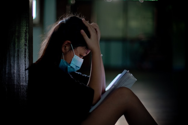 마스크를 쓴 아시아 소녀는 앉아서 스트레스로 책을 읽고 이해하지 못합니다. 국가 검역 중 학습 문제의 개념