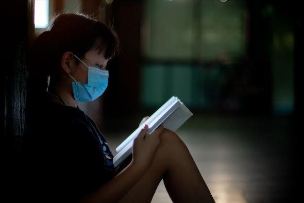 마스크를 쓴 아시아 소녀는 앉아서 스트레스로 책을 읽습니다. 국가 검역 중 학습 문제의 개념