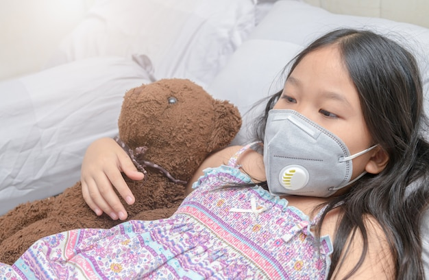 Asian girl wearing a dust mask pm2.5 on bed