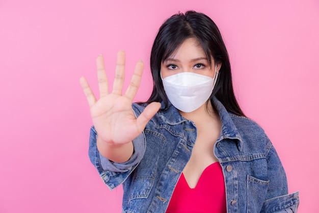 Ragazza asiatica che indossa la maschera per il viso mostra il gesto delle mani per fermare l'epidemia di virus corona, proteggere la diffusione covid-19