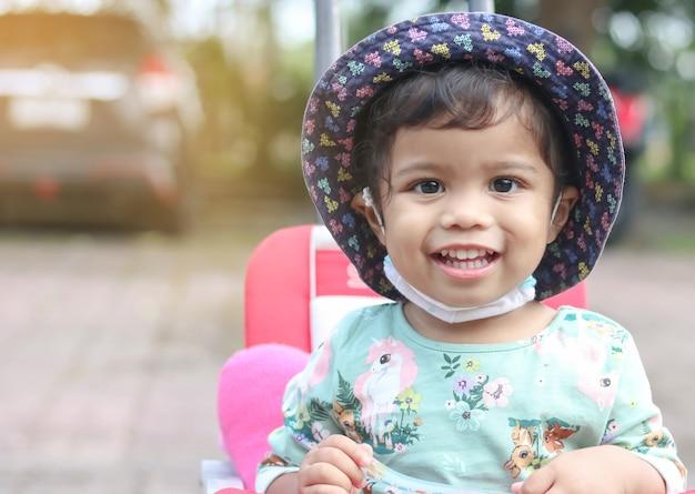 아시아 소녀 모자를 쓰고 미소와 행복의 자에 앉아 턱 아래에 마스크를 넣어.